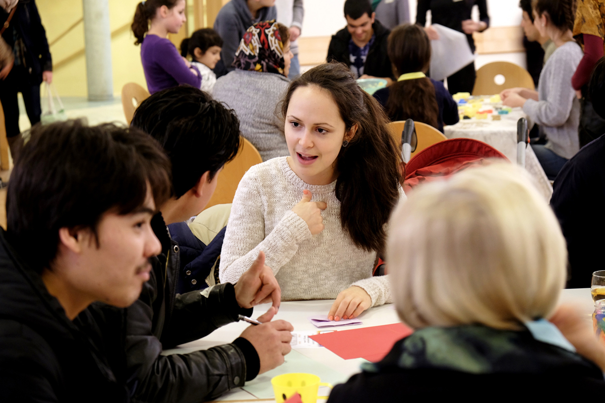 Eine Seminarteilnehmerin kommt im Café Asyl mit einem Flüchtling ins Gespräch.